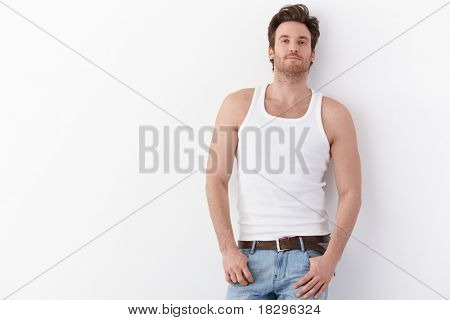 Sexy young man standing by wall in undershirt, smiling.