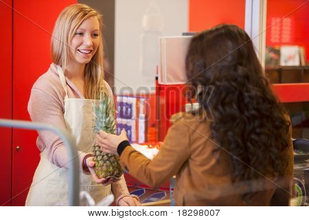 Happy shop assistant with customer in supermarket holding pineapple