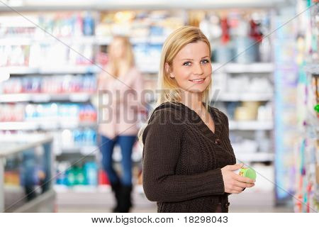Young woman smiling while holding goods in the supermarket with people in the background
