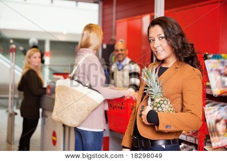 Portrait of a customer carrying pineapple in supermarket with people in the background
