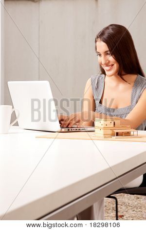 An architect working on a computer with house model on the desk
