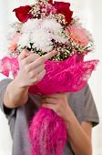 stock photo of indecent  - The teenager with a bunch of flowers shows indecent gesture - JPG