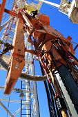 foto of oilfield  - Close up of an oil pump with blue sky - JPG