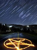 stock photo of magickal  - Pantagram made of fire in the middle of a country rural road at night time with a long exposure of star trails in the sky - JPG