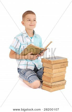 The Young Boy Dreams Near The Open Old Book