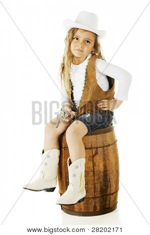 A pretty preschooler sitting on an old wooden barrel while dressed as a cowgirl,  On a white background.