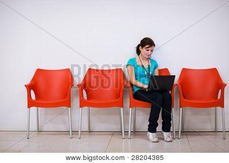 Bastante joven estudiante con ordenador portátil en el campus de la Universidad