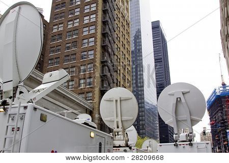 Television media trucks with satellite dishes pointing towards the sky.