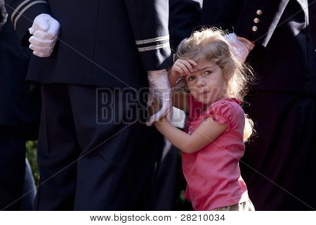 NEW YORK - SEPT 11: An unidentified child stands next to a Firefighter during ceremony at the Firefighters Memorial on September 11, 2011 in New York. Today is the 10TH anniversary of the WTC attacks.