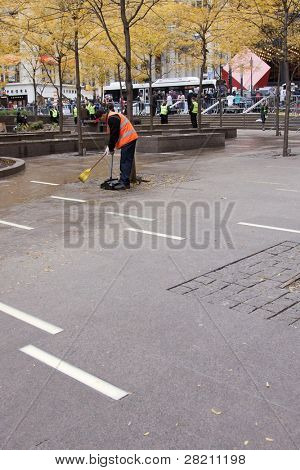 NEW YORK - NOV 17: An unidentified worker cleans Zuccotti Park on the 'Day of Disruption' on November 17, 2011 in New York City, NY. Protesters had occupied the park for 2 months before being evicted.