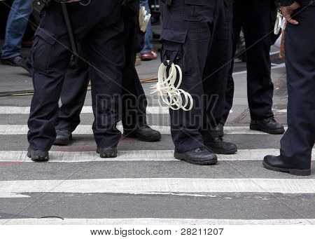 NEW YORK - NOV 17: Police officers equipped with handcuffs stationed on Wall St near the New York Stock Exchange during the Occupy Wall Street rally on November 17, 2011 in New York City, NY.