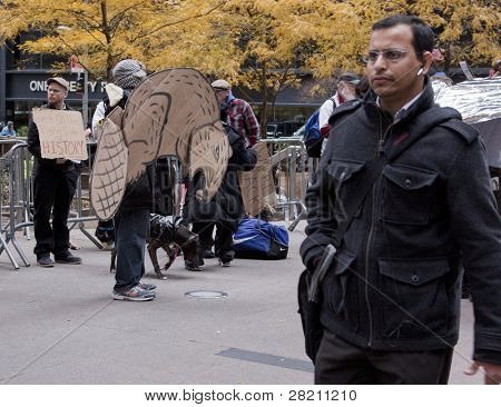 NEW YORK - NOV 17: Pedestrians pass by a man holding a cardboard rat sign in front of Zuccotti Park on November 17, 2011 in New York City. Today marks the 2 month anniversary since the protests began.