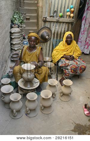 Two Fulani nomad women make pottery from river clay