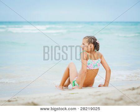 Adorable niña feliz en vacaciones en la playa