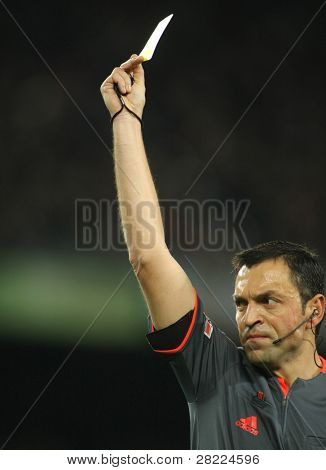 BARCELONA - FEB 6: Referee Teixeira Vitienes delivers yellow card during Spanish soccer league match between FC Barcelona and Getafe at the Nou Camp Stadium on February 6, 2010 in Barcelona, Spain.