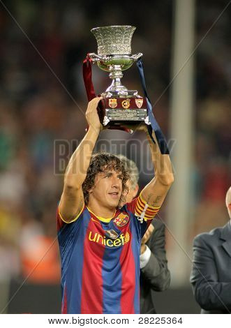 BARCELONA - AUGUST 21: Carles Puyol of Barcelona holds up the spanish Super cup after the match between Barcelona vs Sevilla at the New Camp Stadium in Barcelona on August 21, 2010