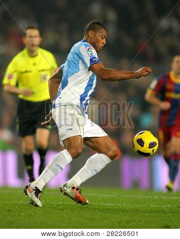 BARCELONA - JAN 16: Julio Baptista of Malaga goes after the ball during the match between FC Barcelona and Malaga CF at the Nou Camp Stadium on January 16, 2011 in Barcelona, Spain