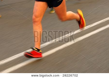 Marathon runner legs on the road with panning blur