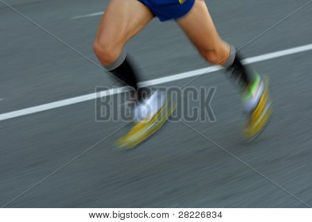Marathon runner legs on the road followed by another runner with panning blur