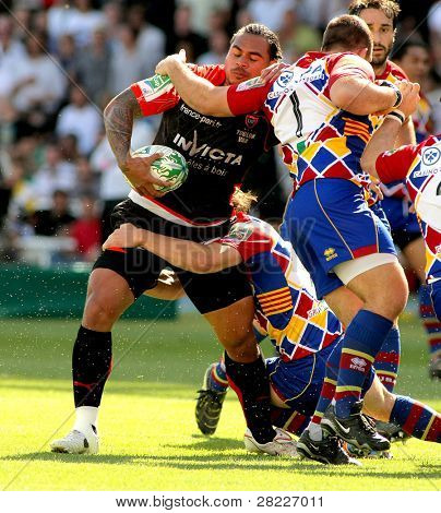 BARCELONA - APRIL 9: Toulons's Christian Loamanu is tackled by Perpignan's player during the Heineken European Cup match against USAP Perpignan at the Olympic Stadium in Barcelona, on April 9, 2011