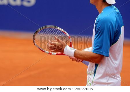 A tennis player prepares to serve a tennis ball during a match