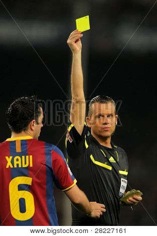 BARCELONA - MARCH 19: Spanish Referee Muniz Fernandez delivers yellow card to Xavi Hernandez during the match between Barcelona and Getafe at the Nou Camp Stadium on March 19, 2011 in Barcelona, Spain