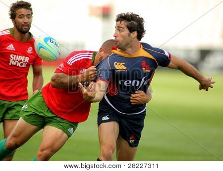 BARCELONA - JULY 9: Martin Heredia of Spain is tackled by Portuguese player during the match of Rugby7 European Champìonship Spain against Portugal at the Olympic Stadium in Barcelona, Spain on July 9, 2011