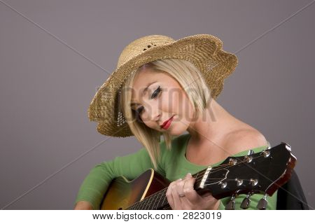 Blonde Playing Guitar In Straw Hat