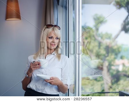 Business Woman Drinking And Staring Out Of Window