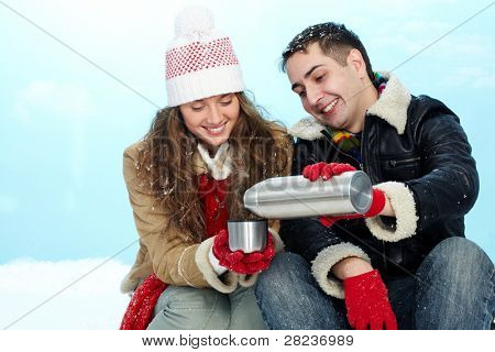 Portrait of happy couple going to drink hot tea on winter day