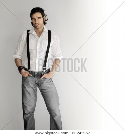 Portrait of a stylish young man in white shirt and suspenders against white background