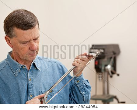 Senior Man Holding A Metal Saw
