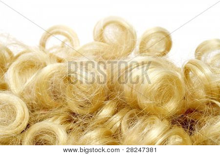 closeup of a curly blonde wig on a white background