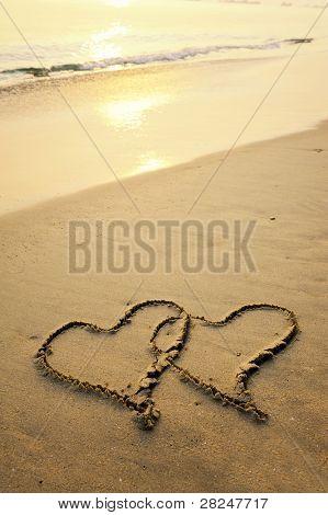 dois corações desenhadas na areia de uma praia