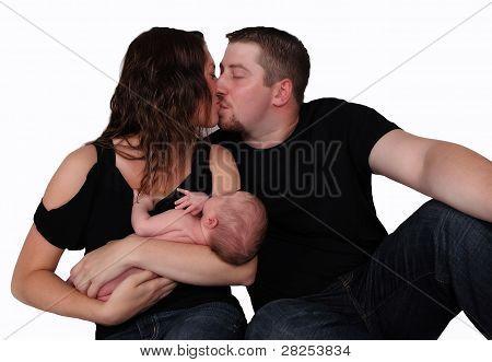 glückliches Paar teilen einen Kuß, wie sie ihr neugeborene Kind zu halten. isoliert