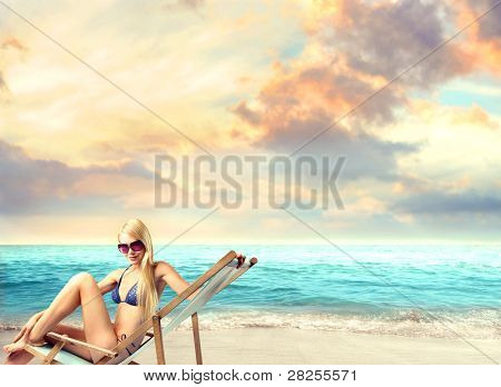Beautiful woman in bikini sitting on a deckchair at the seaside
