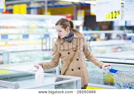 Young woman buying frozen groceries in a supermarket/mall/grocery store (color toned image; shallow DOF)
