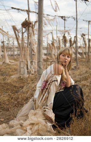 Fashion Girl Sitting In A Field