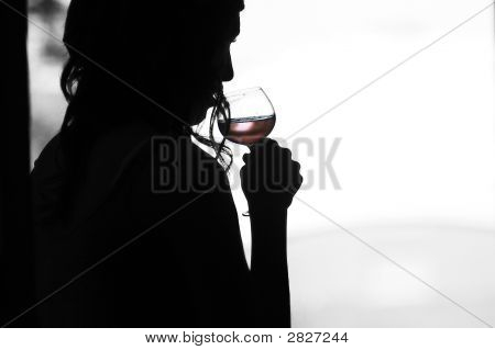 Silhouette Of A Woman Sipping Wine