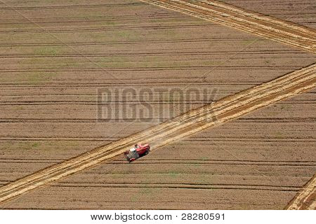 Aerial View : combine harvester working in the fields