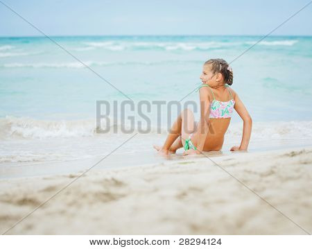 Adorable happy little girl on beach vacation