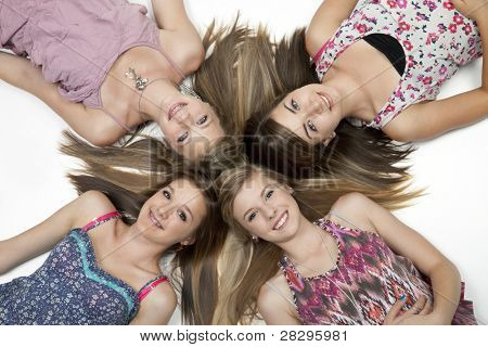 Overhead view of four teenage girls lying on white floor.