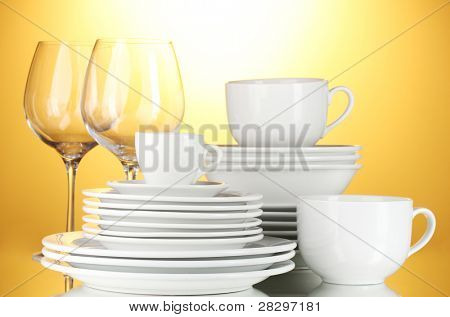 empty bowls, plates, cups and glasses on yellow background