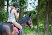 Bay Horse With Young Teenage Girl Equestrian With Smartphone Riding Horseback And Taking Picture In  poster