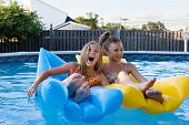 foto of summer fun  - Girls floating together laughing and having fun in the swimming pool - JPG
