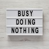 Modern Board With Text busy Doing Nothing On A White Wooden Surface, Top View. From Above, Flat La poster