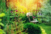 Beautiful Blooming Summer Private Garden With Wooden Chair, Gardener Hat And Watering Can poster