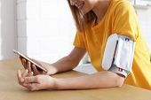 Woman Checking Blood Pressure With Modern Monitor And Smartphone At Table Indoors, Closeup. Cardiolo poster