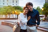 Romantic mature couple enjoying evening walk after office. Cheerful man and beautiful woman embracin poster