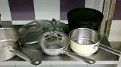 Stainless Steel Pans In The Kitchen Table. Stainless Steel Cookware At Kitchen. Clean Pans And Pots  poster